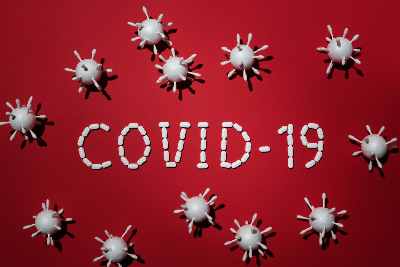 COVID-19 spelled out in pills against a red background surrounded by a dozen virus graphics