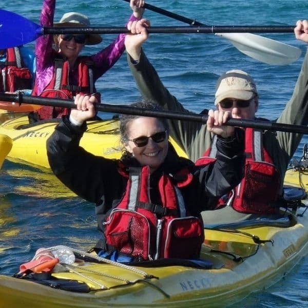 happy kayakers with paddles held above their heads