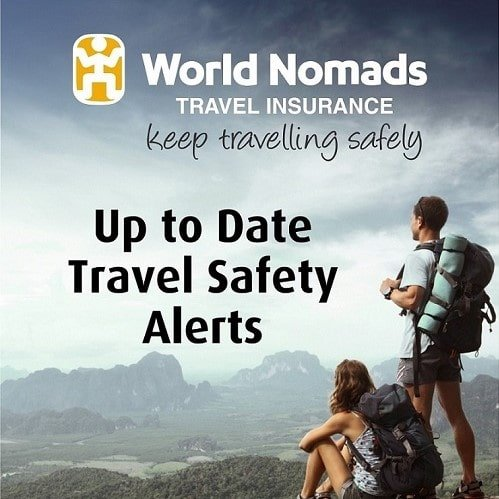 World Nomads Travel Insurance ad with woman sitting with backpack and man standing with backpack