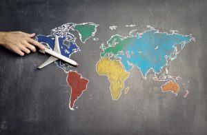 non-detailed world map with hand holding a model plane